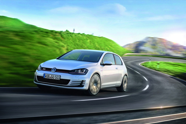 A silver Golf GTI driving on a country road