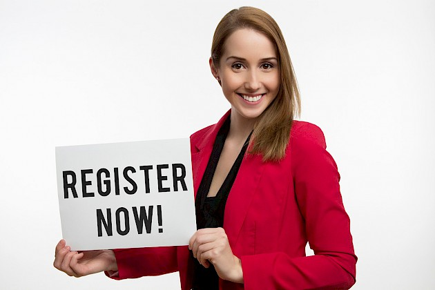 "A woman holding a sign that reads ""Register now!"""