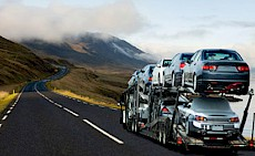 A car carrier driving along a long country road